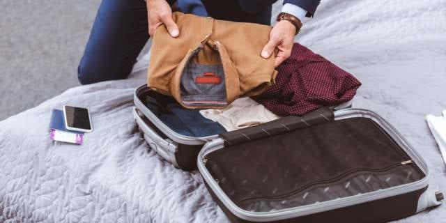 スーツケースに荷物を詰める男性