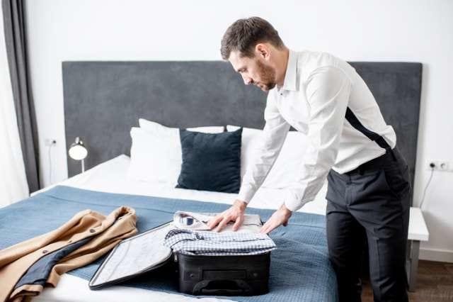 スーツケースに荷物を詰める人