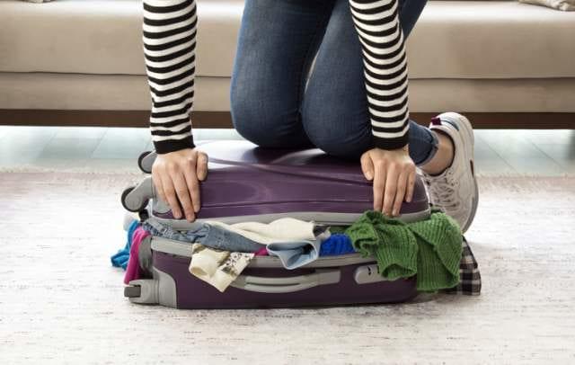 旅行の帰りに荷物をスーツケースに詰める人