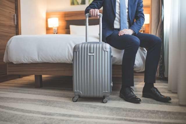 スーツケースで出張する人