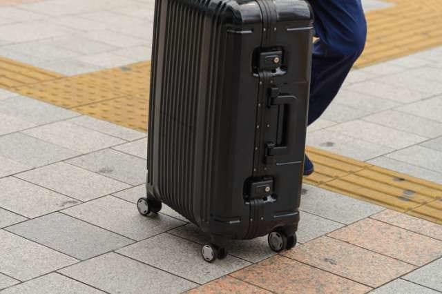 スーツケースを押す人