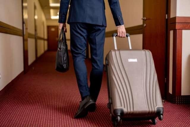 スーツケースとブリーフケースを持つ人