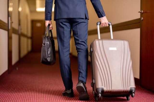 スーツケースとバッグを持つビジネスマン