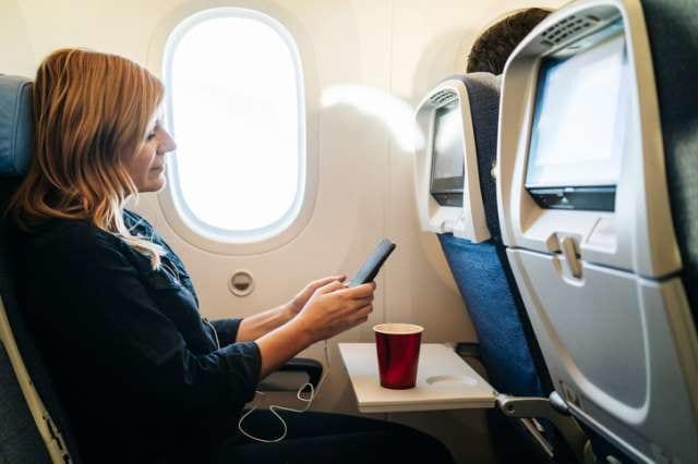 機内でスマホをさわる女性