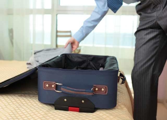 出張用荷物をスーツケースに詰めるビジネスマン
