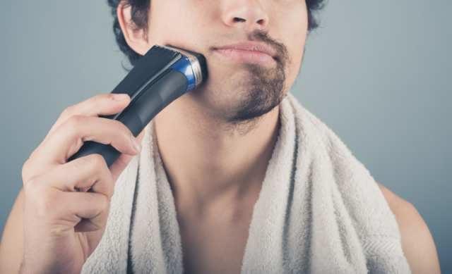 シェーバーで髭を剃る男性