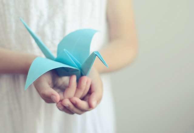 折り紙の鶴を持つ人