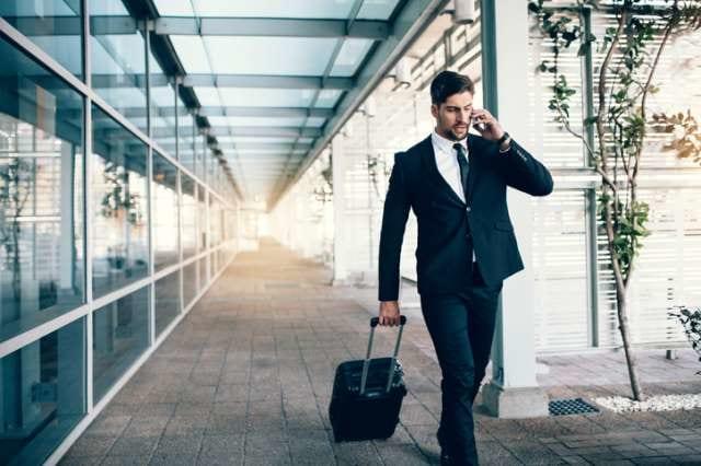 スーツケースを引くビジネスマン