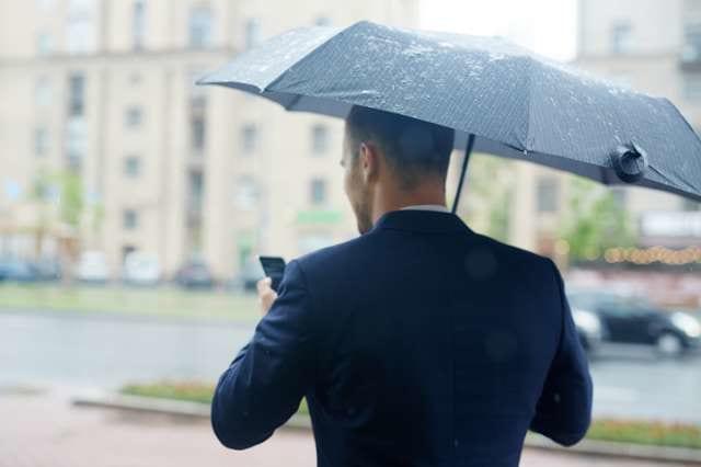 雨に見舞われるビジネスマン