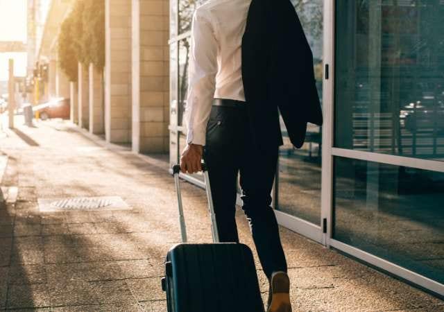 スーツケースを持って移動するビジネスマン