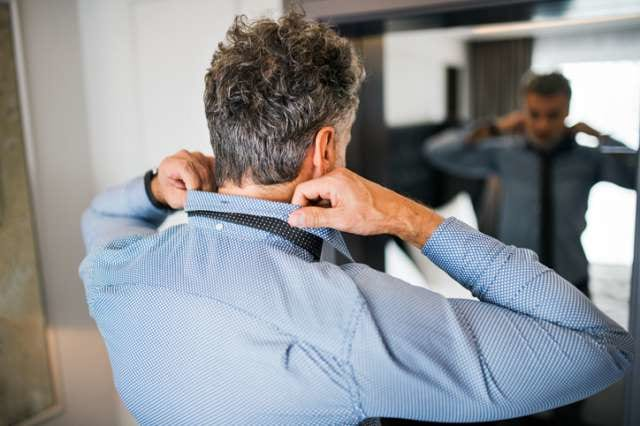 出張先でワイシャツを着る男性
