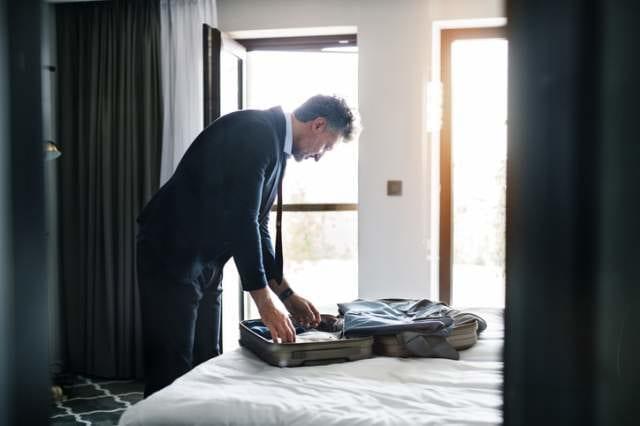 スーツケースに荷物を詰めるビジネスマン