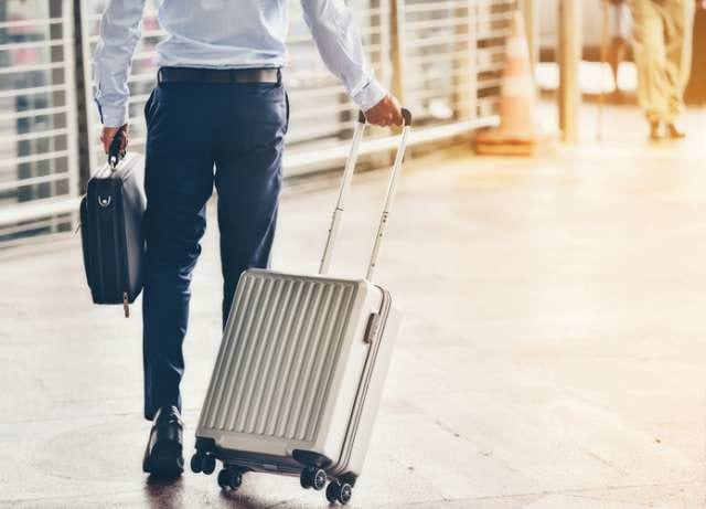 スーツケースを持って歩くビジネスマン