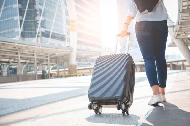 スーツケースを引く旅行者