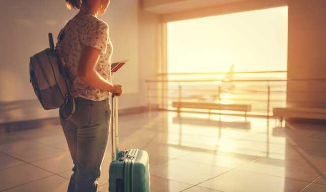 スーツケースを持って飛行機を待つ人