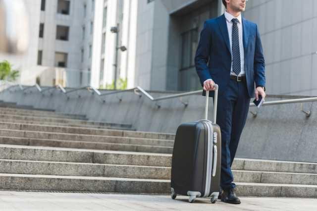 スーツケースを持って移動する男性
