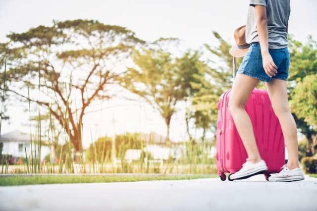 スーツケースを持って移動する旅行者